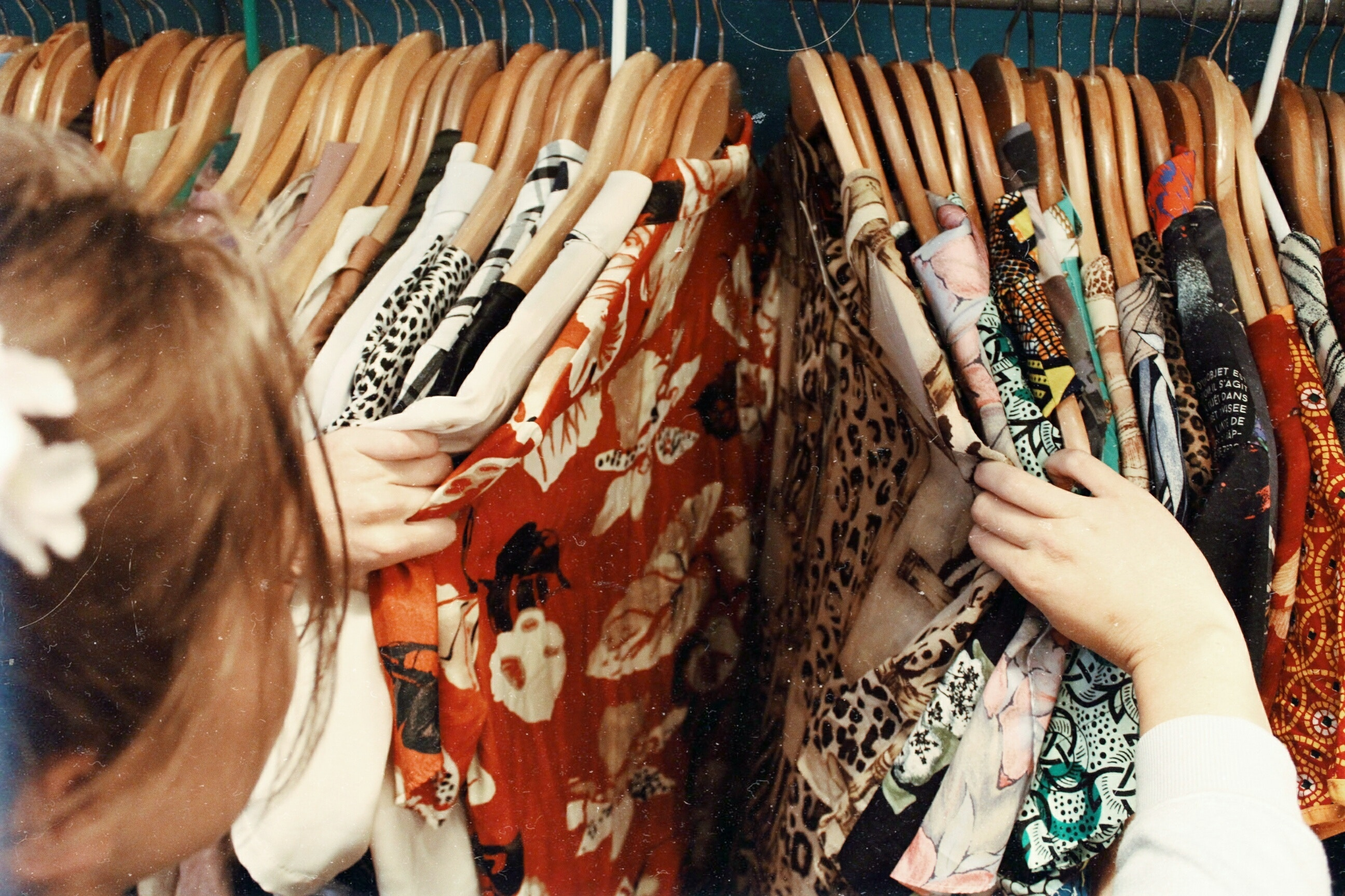 Woman shopping and looking through a rack of clothes.