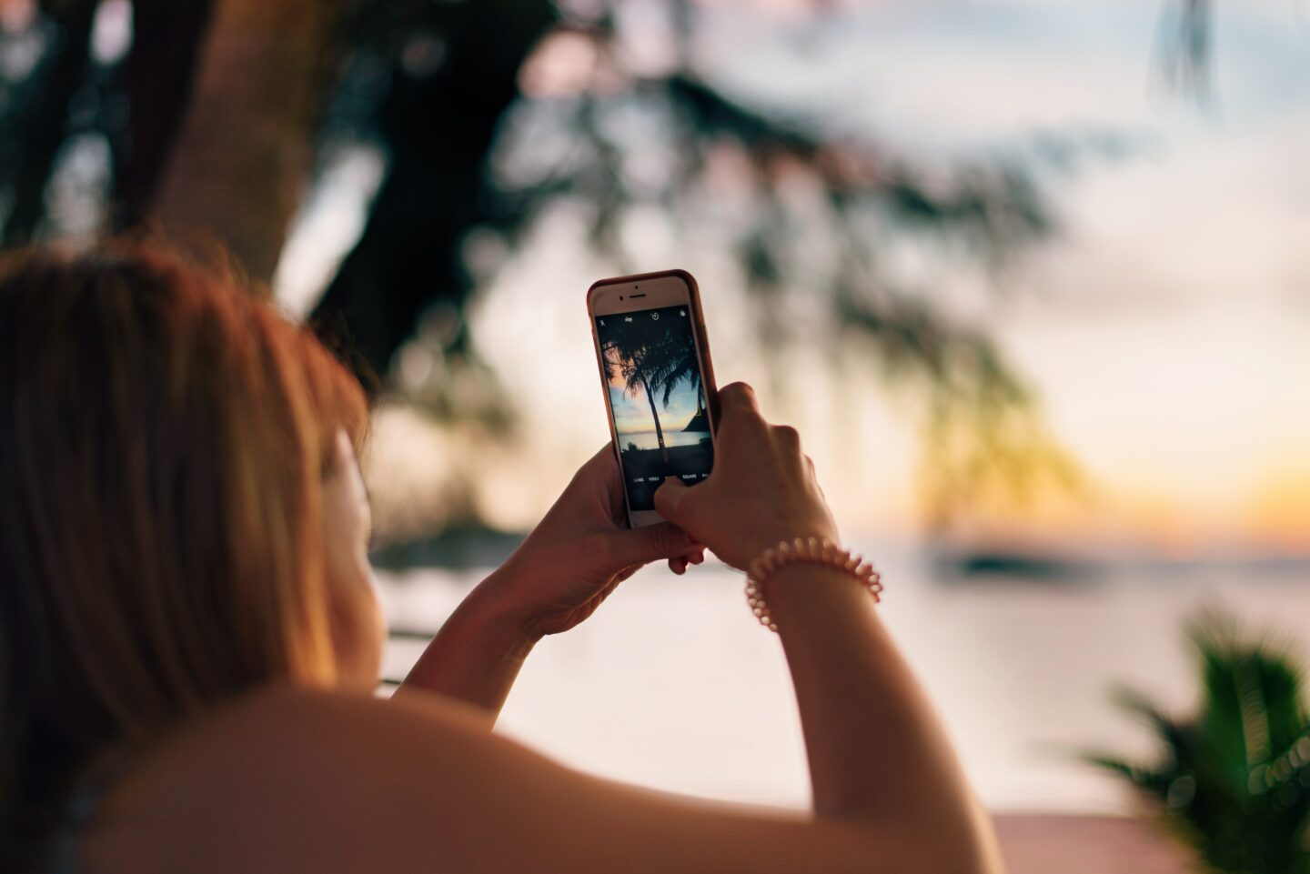 Girl taking a picture of the beach with her phone