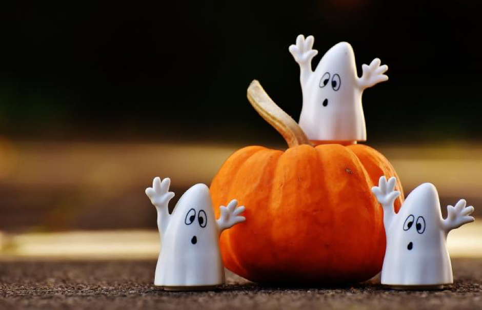 Halloween style photo pumpkin with 3 ghost figurines.