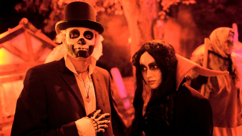 A man and a woman dressed up in Halloween costumes at a party.