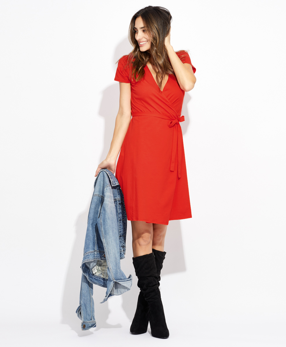 Model posing in a sustainably-made red dress.